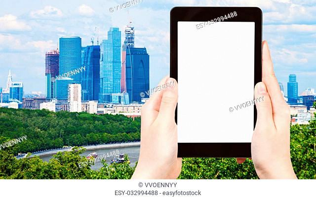 travel concept - tourist photograph cityscape with new Moscow City buildings in spring on tablet pc with cut out screen with blank place for advertising logo