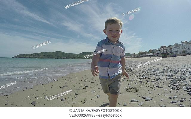 Happy active child boy running on the beach and enjoying sunny day in Spain