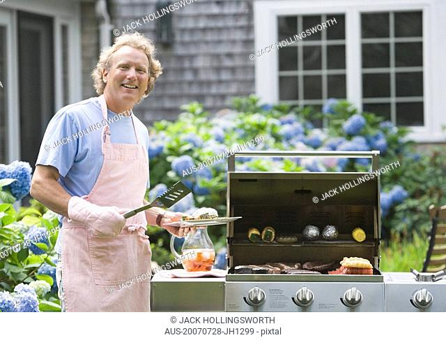Portrait of a mature man cooking food on a barbecue grill