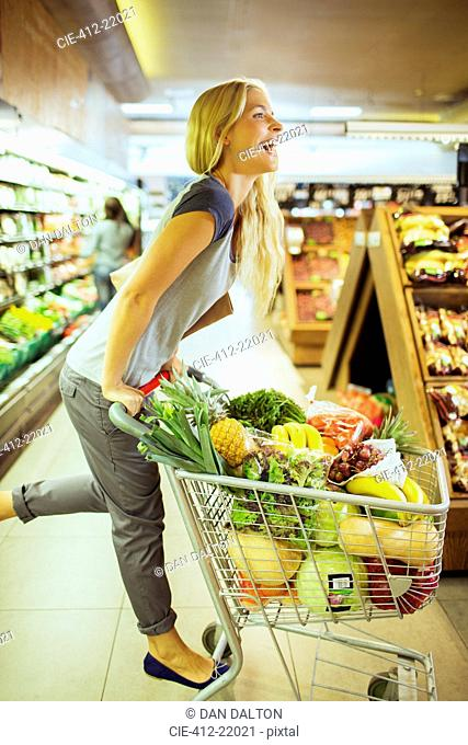 Woman playing on shopping cart in grocery store