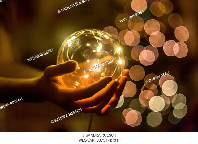 Hands of girl holding shining crystal ball
