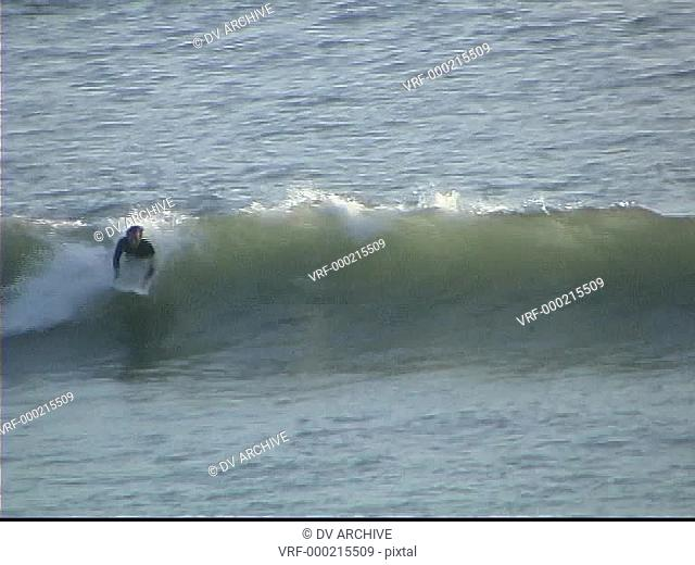 A man successfully surfs across a small wave