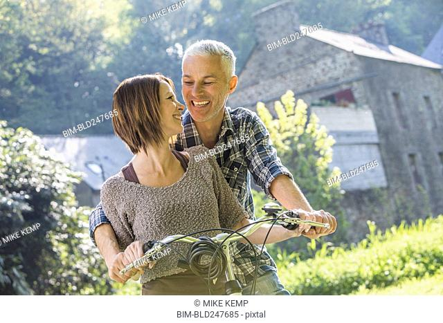 Caucasian couple riding bicycle