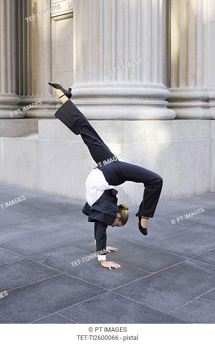 Businesswoman dancing on urban sidewalk
