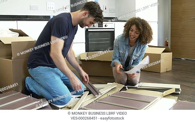 Couple sitting on the floor and following furniture assembly instructions.Shot on Sony FS700 in PAL format at a frame rate of 25fps