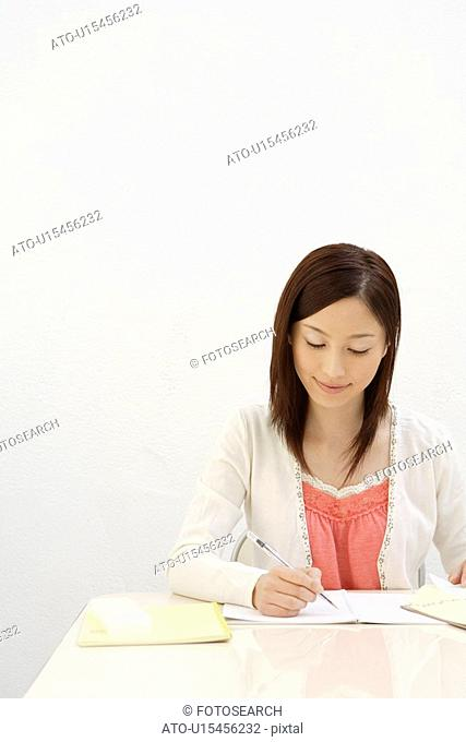 View of a young woman writing