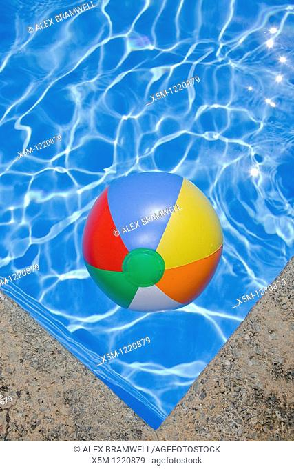 Bright blue swimming pool withj a beachball in the corner