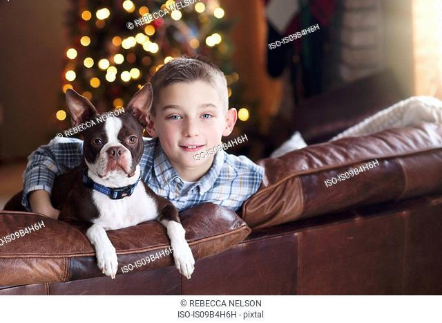 Portrait of young boy sitting on sofa with pet dog