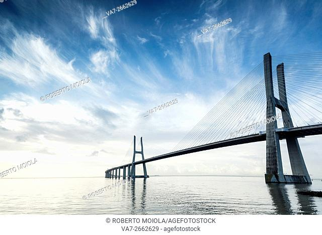 Blue sky and the colors of dawn emphasize the architecture and atmosphere at the Vasco Da Gama Bridge Lisbon Portugal Europe