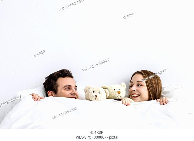 Young couple with teddy bear looking at each other, smiling