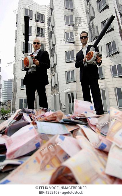 Men in Black, two business people with leaf blowers and banknotes, symbolic of waste of money