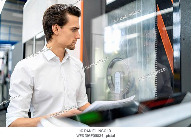 Businessman with manual at a machine in a factory