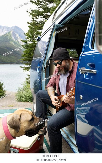 Man with dog playing guitar inside camper van at lakeside