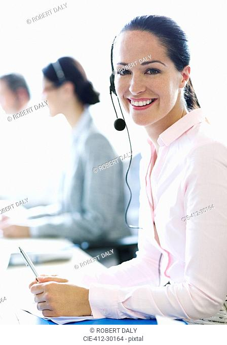 Portrait of smiling businesswoman talking on the phone with headset