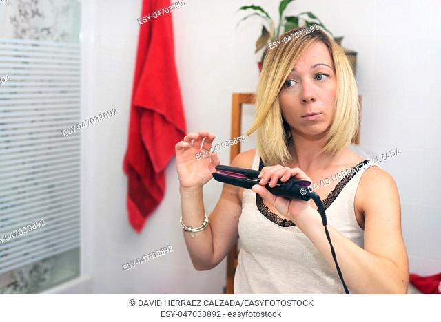 Beautiful natural blond girl using hair iron at home