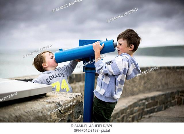 Two boys using coin operated telescopes at the seaside