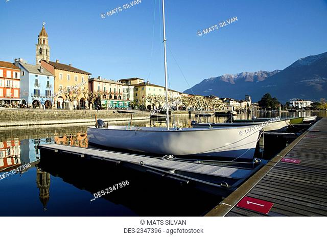 Boats mooring along docks in Lake Maggiore with buildings and the Swiss Alps in the background; Ascona, Ticino, Switzerland