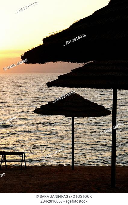 Straw umbrellas on the beach at sunset, Kempinski Hotel, Dead Sea, Jordan, Middle East