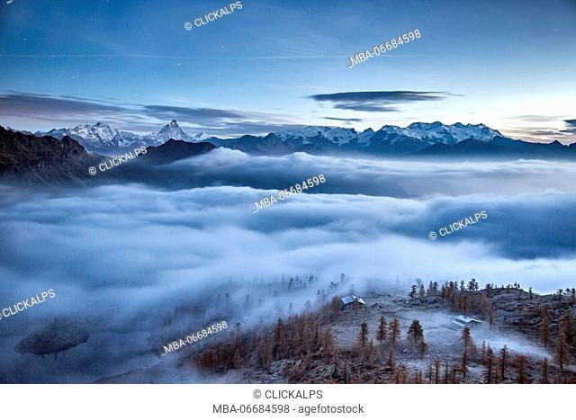 Fog covering Aosta valley at sunrise. Only the Matterhorn and the Monte Rosa emerge like islands from the sea of clouds - Mont Avic natural park, Aosta valley