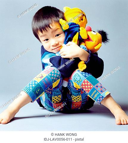 Portrait of a boy playing with a doll