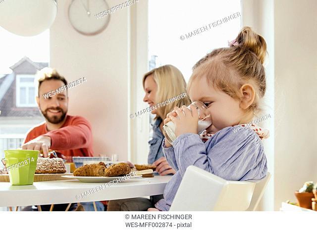 Little girl drinking milk at breakfast table