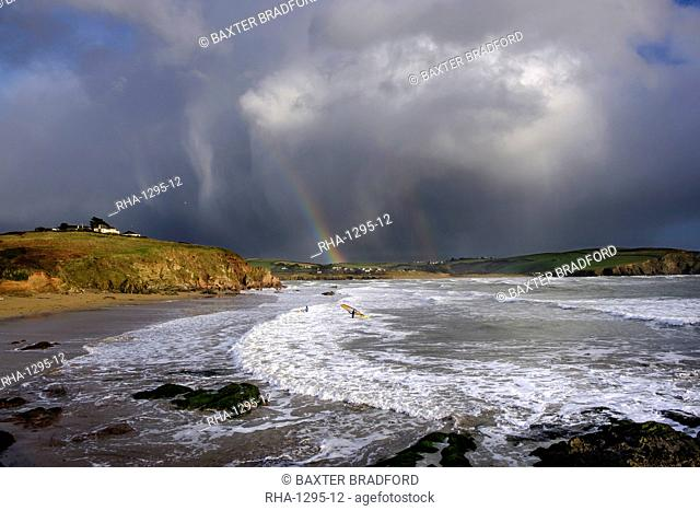 A windsurfer waits to sail out through the surf in stormy weather at Bigbury-on-Sea, Devon, England, United Kingdom, Europe