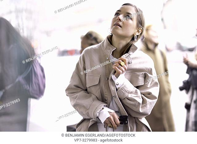 thoughtful fashionable woman looking up, searching for inspiration, during fashion week in Paris, France