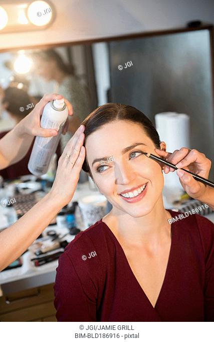 Woman having makeup applied by stylists