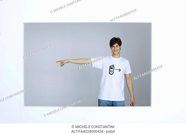 Young man wearing tee-shirt with cell phone graphic, pointing away, smiling at camera