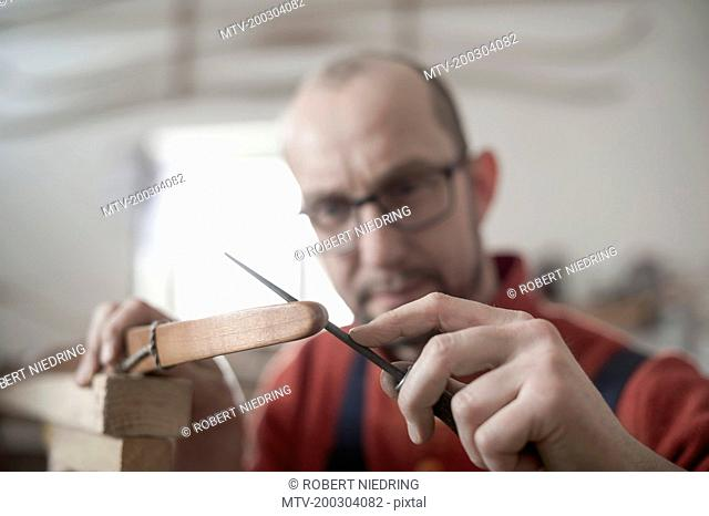 Male bow maker files the tips of a bow in workshop, Bavaria, Germany