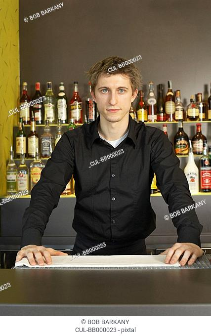 Portrait of young barman behind his bar
