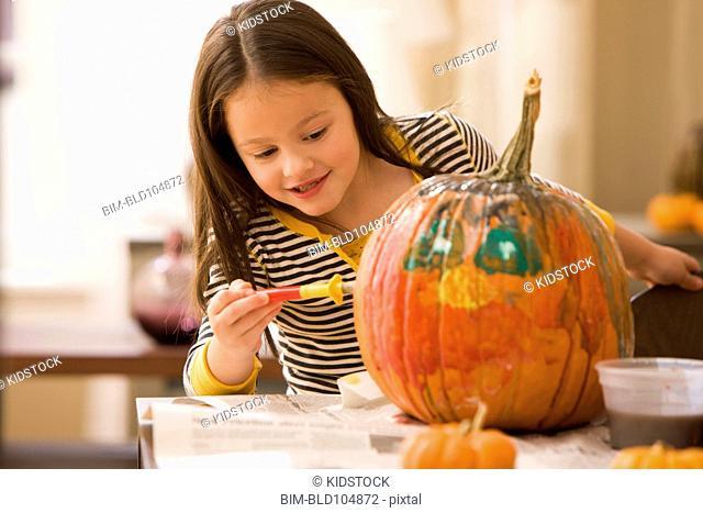 Caucasian girl decorating pumpkin
