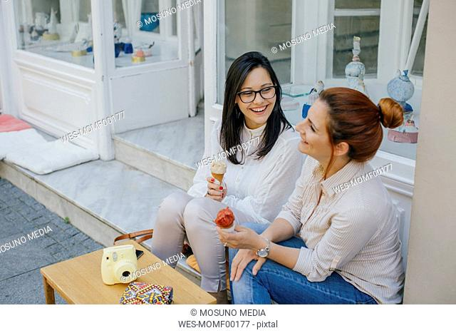 Two friends enjoying ice cream in the city
