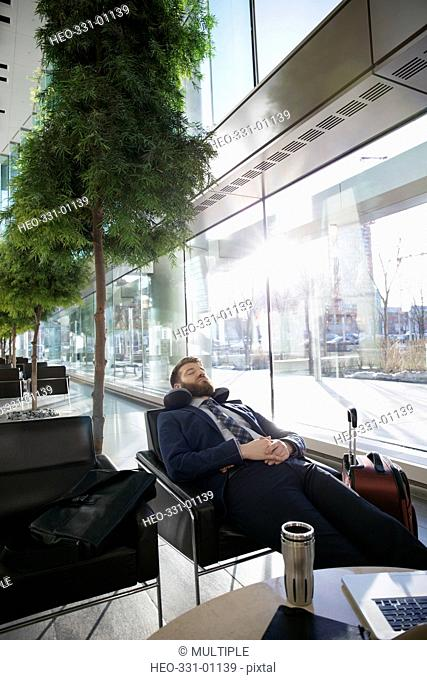 Tired businessman with neck pillow sleeping in airport atrium lounge