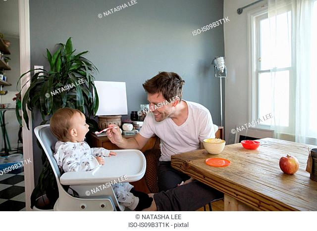 Young boy sitting in highchair, father spoon feeding him food