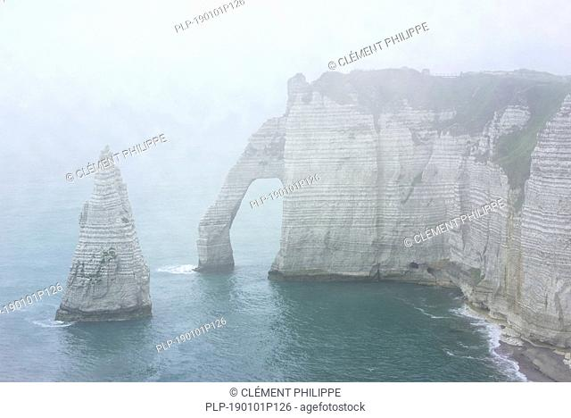 L'Aiguille and the Porte D'Aval, a natural arch in the chalk cliffs at Etretat in the mist, Côte d'Albâtre, Upper Normandy, France
