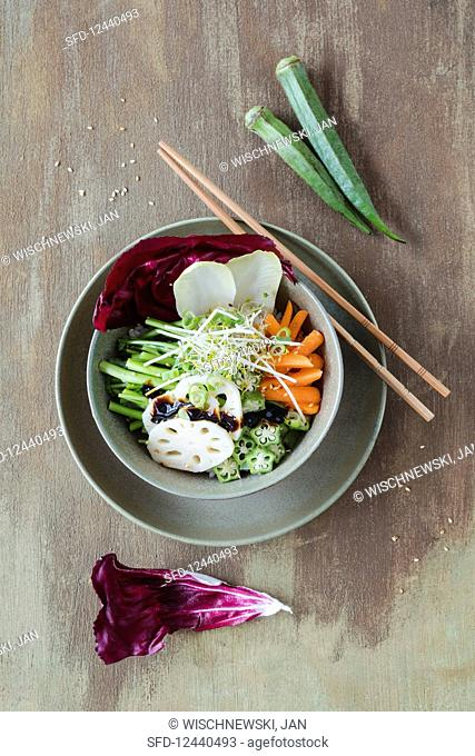 A vegan poke bowl with pickled lotus roots, water spinach, sushi rice, okra and sprouts (Hawaii)