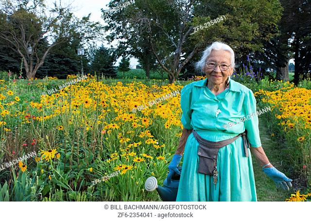 Plain City Ohio 89 year old Amish Great Grandmother watering her flowers in garden in Midwest USA in dress and smile