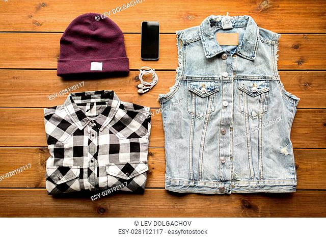 clothing, personal staff and objects concept - casual clothes and smartphone with earphones on wooden background
