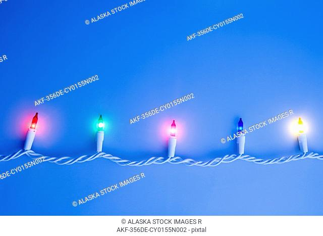 One white strand of multi-colored Christmas tree lights on white background studio portrait with dimmed lighting