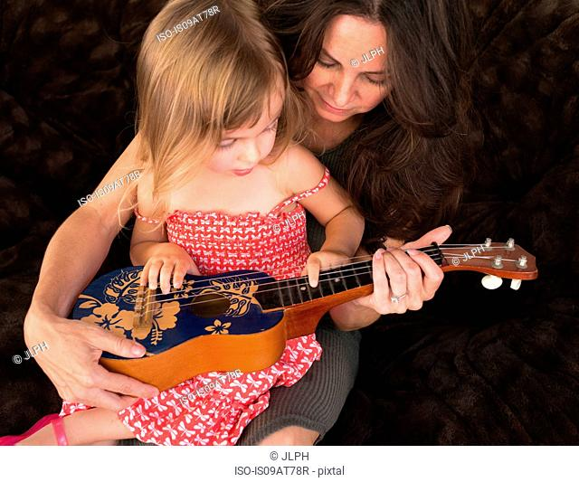 Mother teaching daughter to play the ukulele