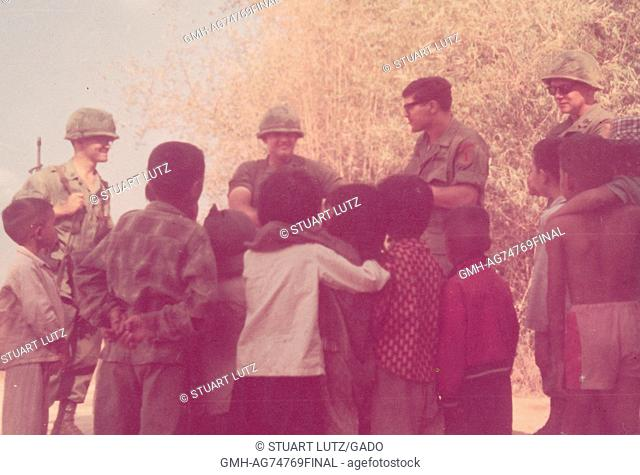 A group of United States Army servicemen speaking to a group of Vietnamese children, the servicemen are all in their combat uniforms and one is carrying his...