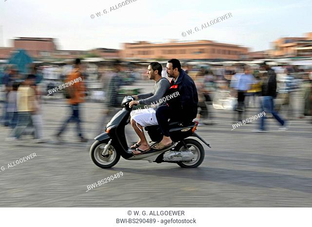 two Moroccans on a motor-scooters crossing Djemaa El Fna , Morocco, Marrakesh, Medina, Djemaa El Fna