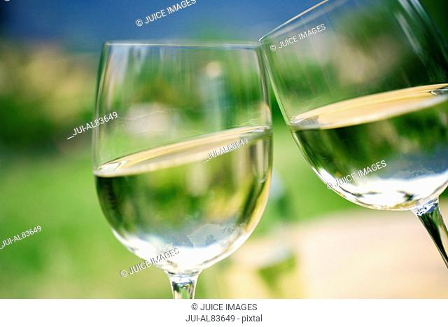 Close up of wine glasses touching outdoors