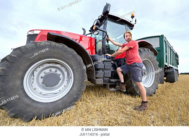 Farmer Climbing Into Cab Of Tractor At Harvest Time