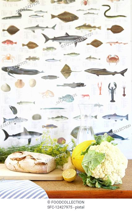 Bread, cauliflower, dill, melon, lemon and a water carafe in front of fish wallpaper