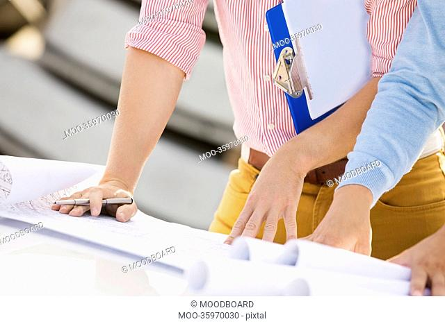Cropped image of architects with blueprints and clipboard