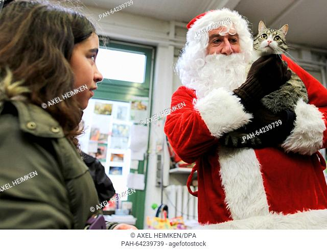 St. Nicholas holds 'Nikolaus' the cat in his arms at the animal shelter on Sueder-Strasse in Hamburg,Germany, 06 December 2015