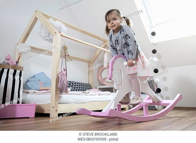 Toddler girl rocking on rocking horse in nursery