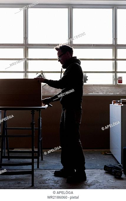 Full length of carpenter measuring wood in workshop